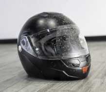 casco de moto integral de color negro con salpicaduras de barro y apoyado sobre el suelo