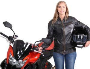 chica joven de pelo rubio y largo vestida de chaqueta negra de cuero sosteniendo un casco integral de moto