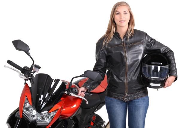 Imagen de una conductora junto a su moto, luciendo su chaqueta de cuero y su casco.