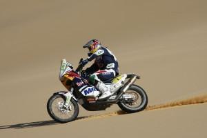 Un piloto con su moto sobre la arena.