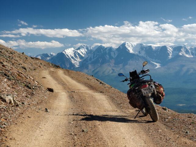 Moto con equipaje aparcada en un camino de tierra