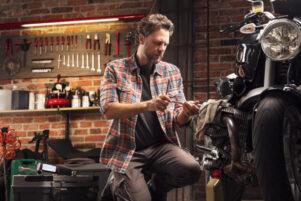 hombre haciendo el manteniemiento de la moto en el garaje de su casa