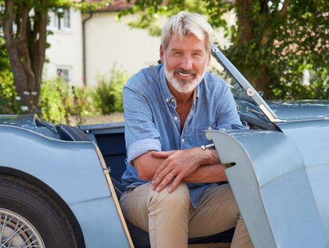 hombre sentado en el asiento de copiloto de un coche clásico