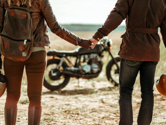 pareja cogida de la mano de espaldas a la camara y con una moto clásica en el campo de fondo