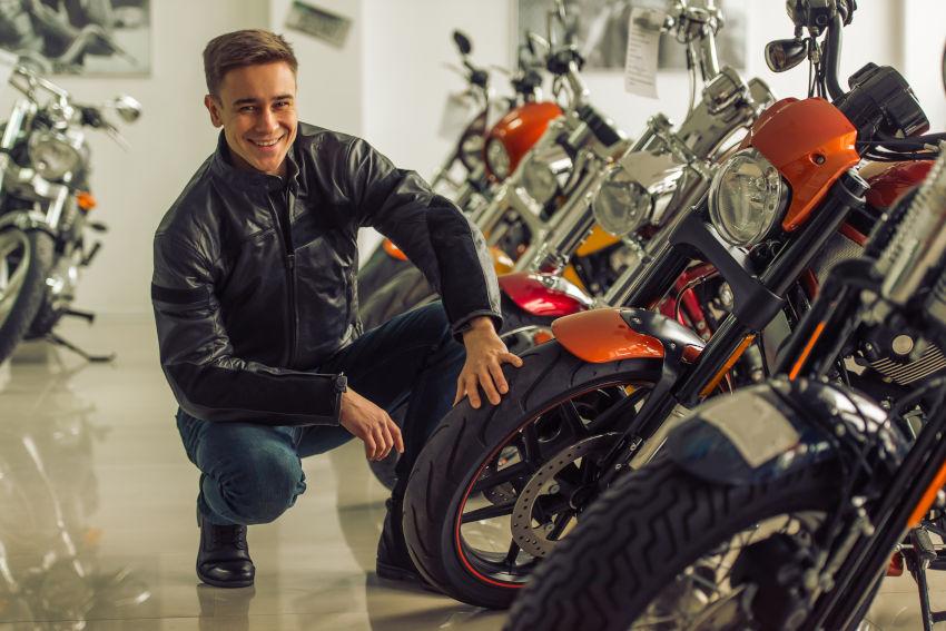 chico joven viendo una exposición de motos en un concesionario