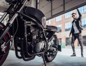 hombre abriendo el portón de un garaje para montar en moto