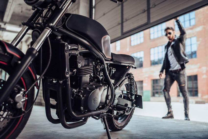 hombre abriendo el portón del garaje para montar en moto