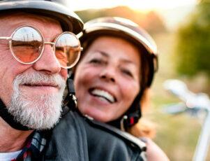 dos personas mayores sonriendo mientras montan en moto