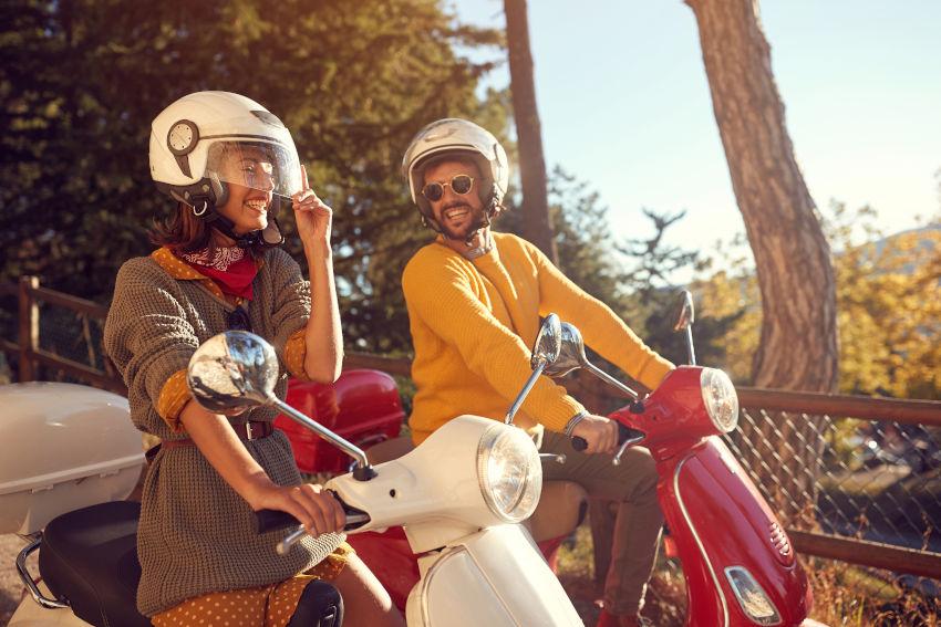 una motera y un motero riendo montados en sus scooters.