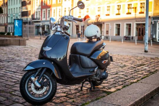 moto 125 automática aparcada en la acera de una ciudad