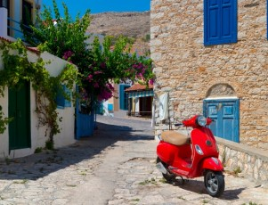 Moto roja de 50cc aparcada en una callejuela