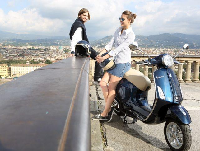 Pareja en mirador de una ciudad con scooter parada