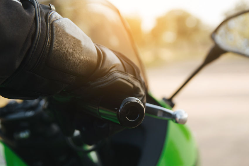 mano de un motorista con guante de protección agrrando el puño acelerador