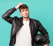 chico joven vestido con camiseta blanca y chaqueta de cuero, rascándose la cabeza con una mano y sosteniendo un casco de moto con la otra