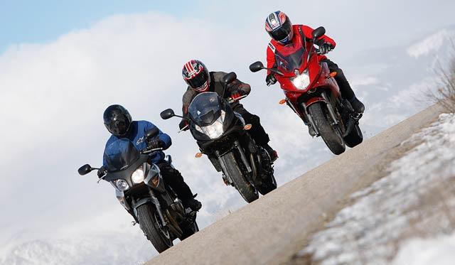 tres motoristas conduciendo en una carretera helada