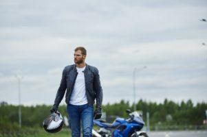 Hombre joven con casco en la mano y a su espalda la moto aparcada