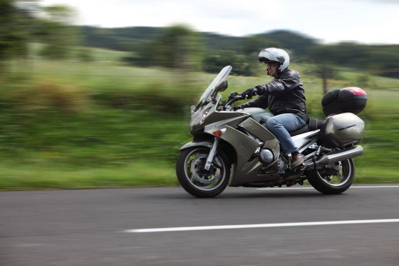 hombre conduciendo una moto gran turismo por la carretera