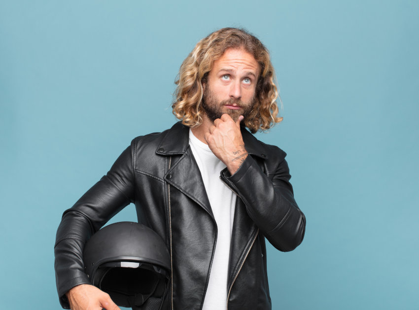 Hombre con el pelo largo rizado y rubio con ropa motera y pose pensativa