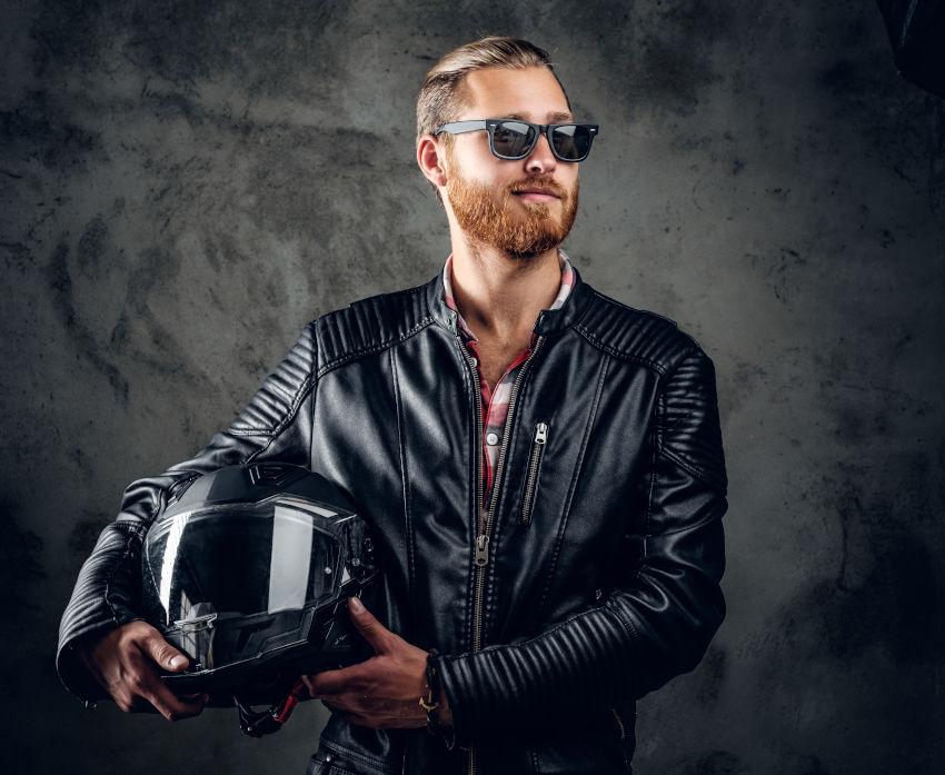 hombre joven con chaqueta de cuero que sujeta en sus brazos un casco de moto integral