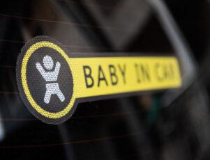 "pegatina ""bebé a bordo"" en la luna trasera de un coche"