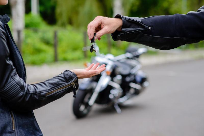 primer plano de las manos de dos personas intercambiando unas llaves, y en segundo plano una moto aparcada