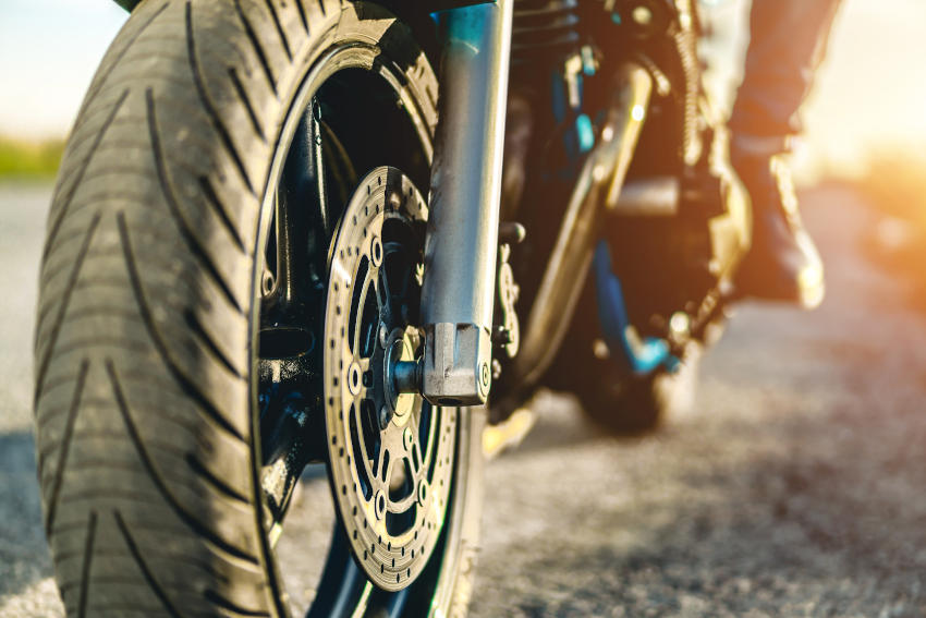plano de la rueda delantera de una moto. Al fondo de la imagen se puede ver el pie del motorista preparado para arrancar