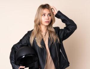 mujer joven vestida con chaqueta de cuero negra, rascándose la cabeza con una mano y sujetando un casco de moto en la otra