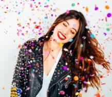 Chica joven con chaqueta de cuero mientras cae confeti