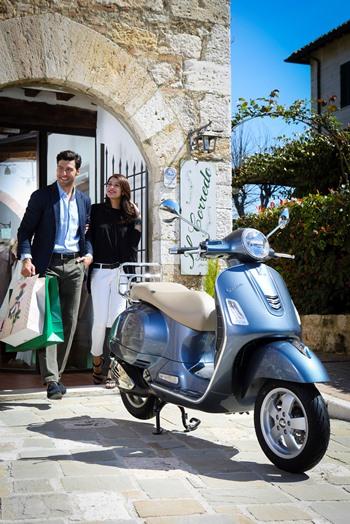 Regalos para moteros: una pareja sale de un restaurante, llena de bolsas de compras, en busca de su moto, aparcada en la puerta.