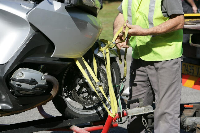 Hombre con chaleco amarillo remolcando una motocicleta