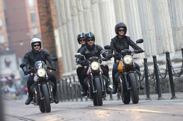 Grupo de motoristas con acompañantes por una calle
