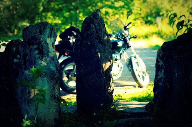 Imagen de una moto aparcada en un paisaje de árboles y rocas.