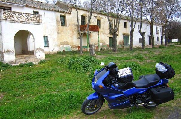 Imagen de una moto aparcada sobre el césped delante de un caserío.