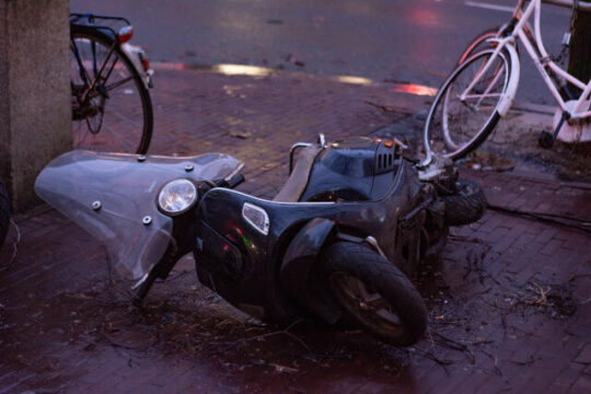 scooter volcado en un andén tras noche de tormenta