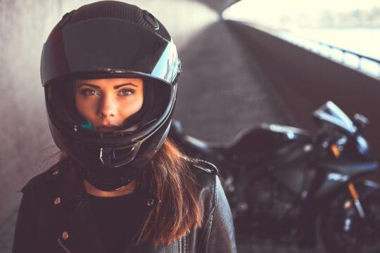 primer plano de una mujer con un casco integral de moto negro. En segundo plano se ve su moto de gran cilindrada aparcada.
