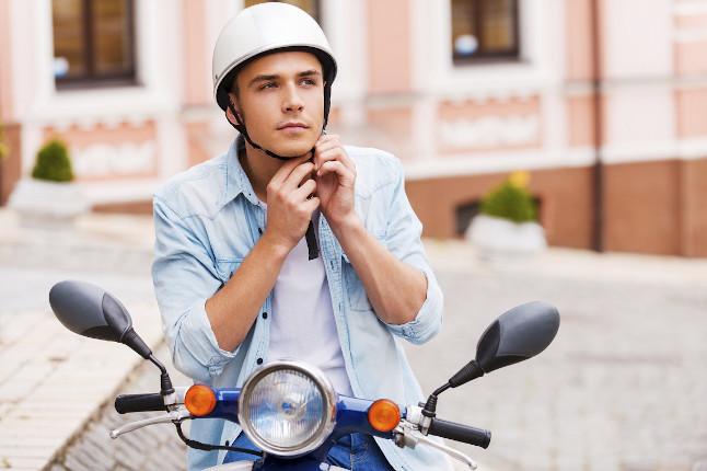 Chico joven abrochándose el casco encima de la moto
