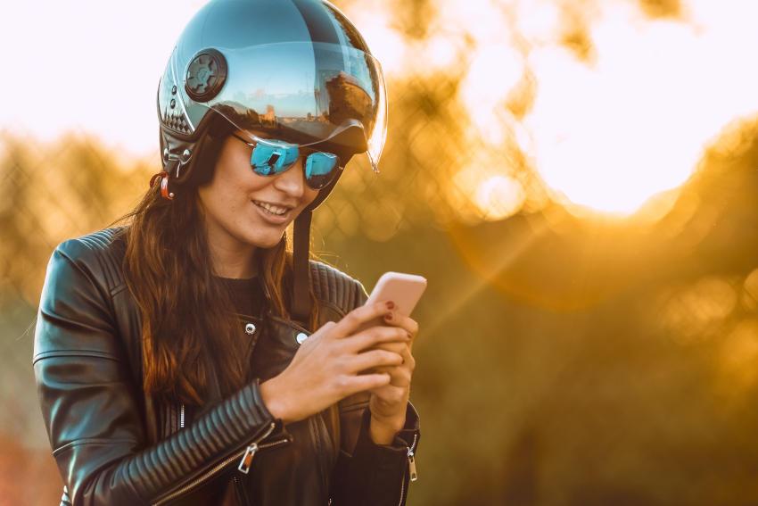 mujer con casco y chaqueta moteros con un smartphone en la mano