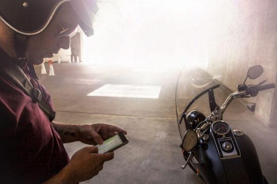 Un motorista mira el móvil al lado de su moto.