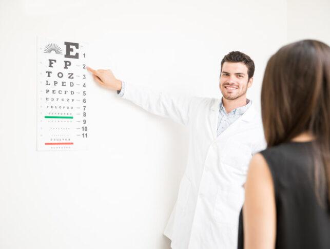 médico pasando el test psicotécnico oftalmológico a una mujer que está de espaldas