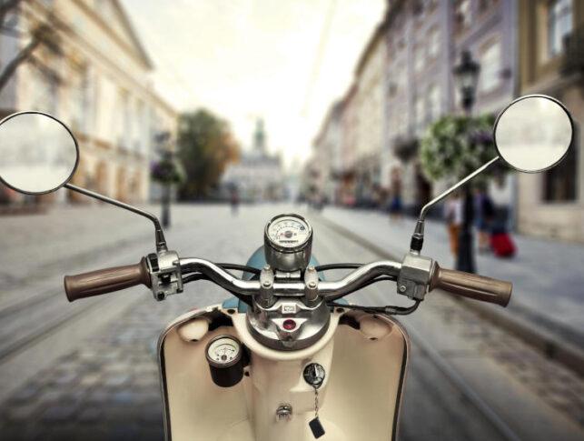 moto en primer plano y al fondo imagen de la calle de una ciudad vacía