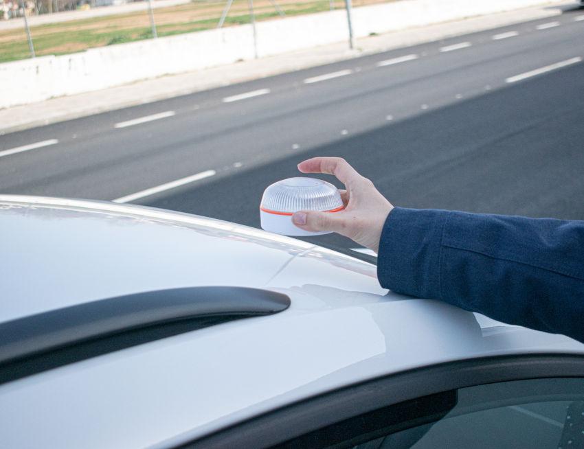 persona colocando una señal v16 en el techo de un coche blanco