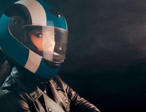 mujer motera con casco integral y chaqueta de cuero mirando de perfil sobre un fondo negro con bruma