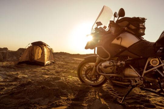 moto trail aparcada y una tienda de campaña en una zona de tierra al atardecer