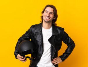 hombre joven sonriente con chaqueta de cuero y sujetando un casco con el brazo derecho